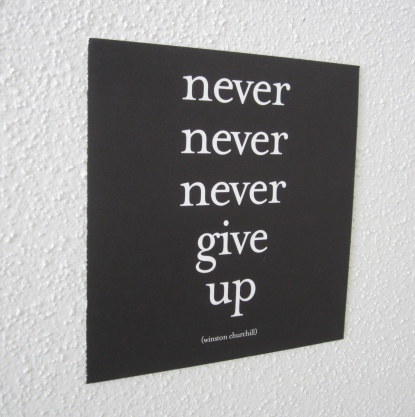 Never Never Never Give Up notecard on the wall